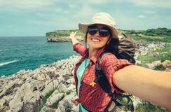 Happy woman backpacker traveler take a selfie photo on amazing o. Cean coast royalty free stock photo