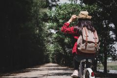 Happy woman backpacker with white bicycle in nature background. Relax time on holiday  travel concept color of hipster style selective and soft focus Stock Photos