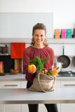 Happy woman with bag of fresh produce holding out an apple Royalty Free Stock Images