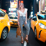Happy woman with a bag in night New York City Times Square street enjoy the summer vacation and smiling with yellow taxi around. Royalty Free Stock Photo