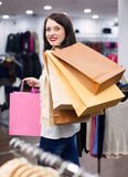 Happy woman with bags. Cute woman with a lot of shopping bags at fashionable store Royalty Free Stock Photos