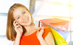 Happy woman with  bags on shopping and kredit card talking on ph Royalty Free Stock Photography
