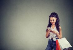 Happy woman with bags shopping online. Excited trendy girl with papers bags using smartphone for shopping in Internet smiling on gray background Stock Photography