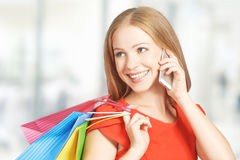 Happy woman with  bags on shopping, talking on phone Royalty Free Stock Image