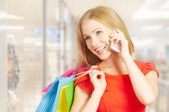 Happy woman with  bags on shopping, talking on phone Royalty Free Stock Images