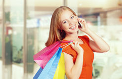 Happy woman with  bags on shopping, talking on phone. Happy woman with  bags on a shopping, talking on the phone Royalty Free Stock Images