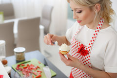 Happy woman baking in her kitchen. Stock Image