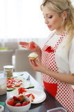 Happy woman baking in her kitchen. Royalty Free Stock Photo