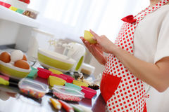 Happy woman baking in her kitchen. Royalty Free Stock Image