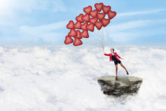 Happy woman and balloons above clouds Stock Photo