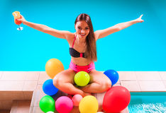 Happy woman with balloons and cocktail at poolside Stock Image