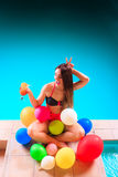 Happy woman with balloons and cocktail at poolside. Happy woman having fun with balloons and cocktail drink alcohol. Pretty attractive girl relaxing at swimming Royalty Free Stock Photos