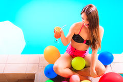 Happy woman with balloons and cocktail at poolside Royalty Free Stock Photography