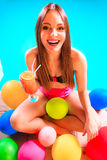 Happy woman with balloons and cocktail at poolside Royalty Free Stock Image