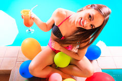 Happy woman with balloons and cocktail at poolside. Happy woman having fun with balloons and cocktail drink alcohol. Pretty attractive girl relaxing at swimming Stock Photography