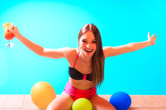 Happy woman with balloons and cocktail at poolside. Happy woman having fun with balloons and cocktail drink alcohol. Pretty attractive girl relaxing at swimming Royalty Free Stock Photography