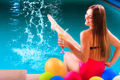 Happy woman with balloons and cocktail at poolside Royalty Free Stock Photos