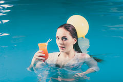 Happy woman with balloons and cocktail in water. Happy woman with balloons and cocktail drink alcohol in swimming pool water. Pretty attractive girl relaxing Royalty Free Stock Image