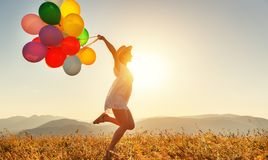 Happy woman with balloons at sunset in summer Stock Image