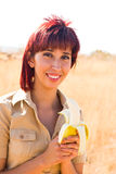 Happy woman and banana. Woman eats a banana fruit with calcium and potassium outdoors Stock Images