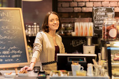 Happy woman or barmaid at cafe counter Stock Image