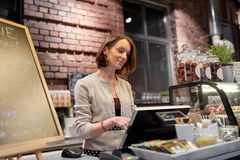 Happy woman or barmaid with cashbox at cafe Stock Photography