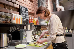 Happy woman or barmaid cooking at vegan cafe Royalty Free Stock Photo