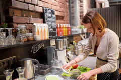 Happy woman or barmaid cooking at vegan cafe Royalty Free Stock Photography