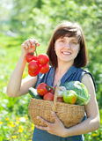 Happy woman with basket of harvested vegetables