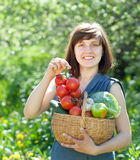 Happy  woman with basket of harvested vegetables Stock Photo