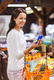 Happy woman with basket and smartphone in market Stock Image