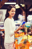 Happy woman with basket and smartphone in market Stock Photography