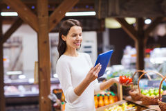 Happy woman with basket and tablet pc in market Royalty Free Stock Images