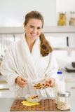 Happy woman in bathrobe making healthy breakfast Stock Images
