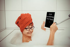 Happy woman in bathtub with tablet computers Stock Photos