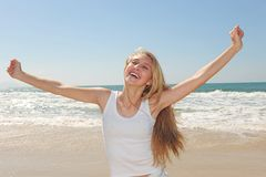 Happy woman on the beach. Laughing stock photography