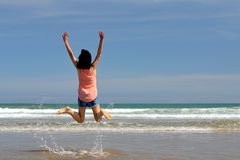 Happy woman on the beach. Woman jumping on the beach Royalty Free Stock Image