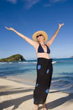 Happy woman on the beach. A happy mature woman raises her hands at the beach Royalty Free Stock Photo
