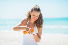 Happy woman on beach applying sun screen creme Royalty Free Stock Images