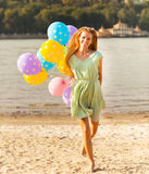 Happy woman on the beach with colored polka dots balloons Royalty Free Stock Image