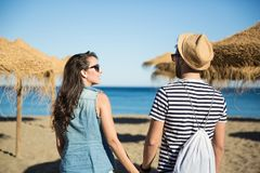 Happy woman on beach holding her boyfriend by hand Stock Image