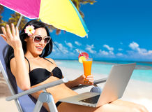 Happy woman on the beach with a laptop. Computer. Vacation and communication concept stock photo