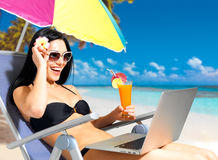 Happy woman on the beach with a laptop. Computer. Vacation and communication concept stock photos
