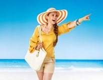 Happy woman on beach pointing at something. Perfect summer. happy woman in shorts and yellow blouse with white beach bag on the beach pointing at something Stock Image