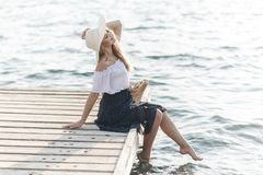 Portrait of a cute girl outdoors in sitting on a pier in the spring. Happy woman on the beach. Portrait of a beautiful girl close-up. Spring portrait on the royalty free stock photos