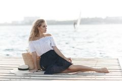 Portrait of a cute girl outdoors in sitting on a pier in the spring. Happy woman on the beach. Portrait of a beautiful girl close-up. Spring portrait on the stock photography