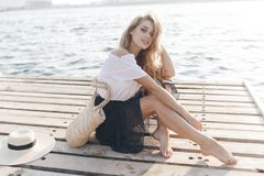 Portrait of a cute girl outdoors in sitting on a pier in the spring. Happy woman on the beach. Portrait of a beautiful girl close-up. Spring portrait on the stock image