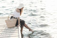 Portrait of a cute girl outdoors in sitting on a pier in the spring. Happy woman on the beach. Portrait of a beautiful girl close-up. Spring portrait on the royalty free stock images