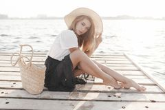 Portrait of a cute girl outdoors in sitting on a pier in the spring. Happy woman on the beach. Portrait of a beautiful girl close-up. Spring portrait on the stock images