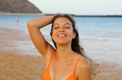 Happy woman on the beach. Portrait of beautiful girl with closed eyes and wind fluttering hair. Summer portrait on the beach at. Sunset. Young pretty smiling royalty free stock photography
